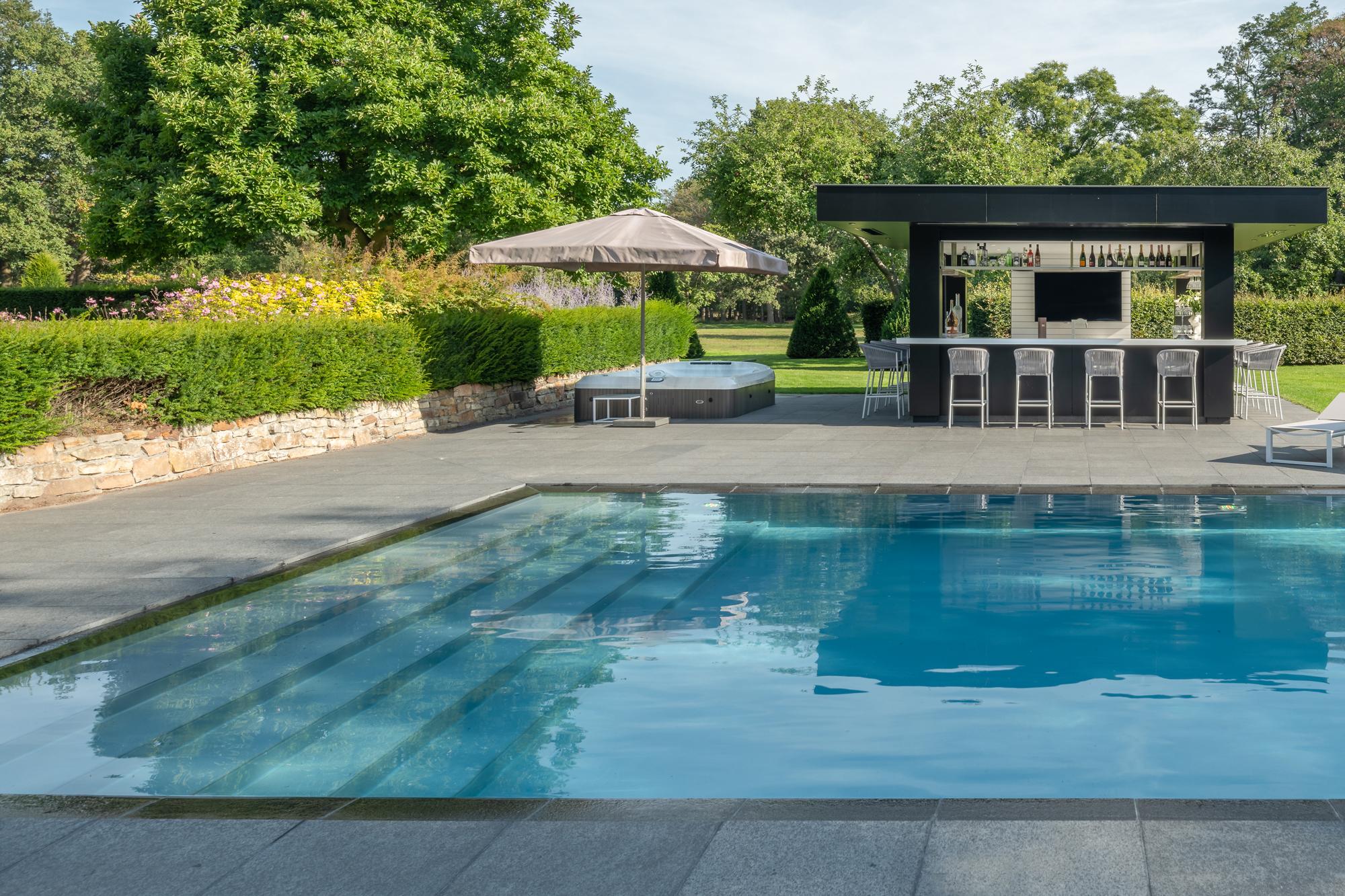 Ein XXL Custom Schwimmbecken in perldunkelgrau mit Malaga Treppe entsprechend von Veltmann Fertigschwimmbecken