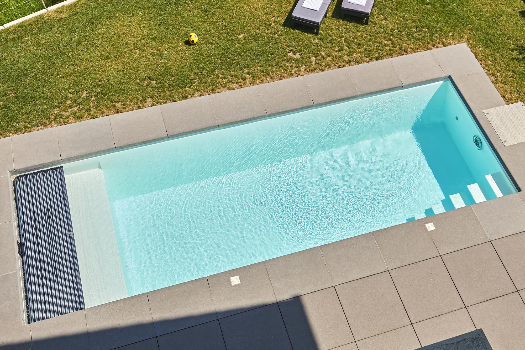 Schwimmbecken mit Liegebank und Solar Rollladenabdeckung in weiß